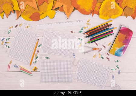Empty white papers and school supplies on wooden table with painted leaves. - Stock Photo