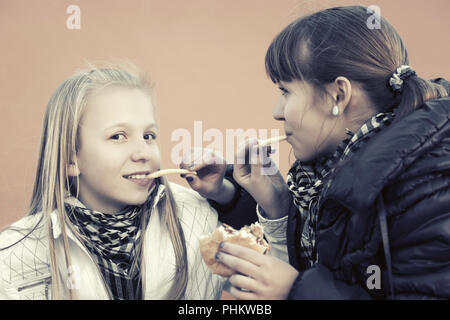 Happy teen girls eating a burgers and french fries - Stock Photo