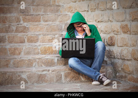 Young man using laptop on city street - Stock Photo