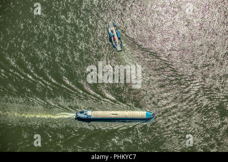 Aerial view, cargo ship on the Rhine goes downhill, closed barge, bulk freighter, meets Rhine ferry near Walsum, vertical view, inland navigation Duis - Stock Photo