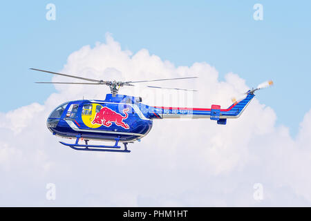 Oshkosh, WI - 28 July 2018:  A Redbull helicopter  flying to advertise the Redbull brand at an airshow - Stock Photo