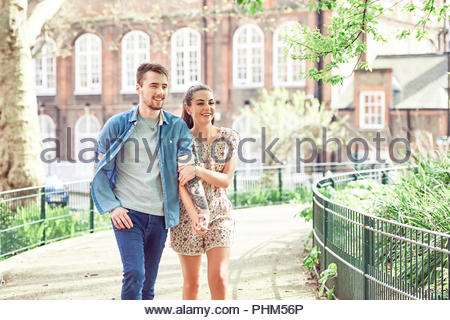 Teenage couple walking in park - Stock Photo