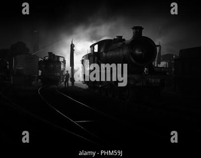 Ex GWR locomotives at night on shed at Didcot Railway centre in a re-created scene reminiscent of the days of steam. - Stock Photo