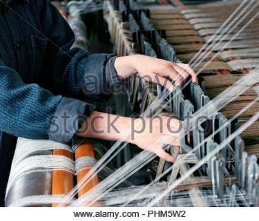 Hands of woman using loom - Stock Photo