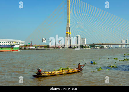 Local boat with one person rowing in a boat close to the big bridge span on the Chao Praya River in Bangkok. - Stock Photo