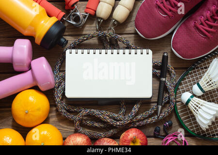 Fitness and healthy active lifestyle dieting background with blank space notebook for your text. Dumbbell, jump ropes, apples, badminton, oranges and  - Stock Photo