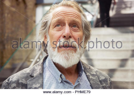 Portrait of senior man looking up - Stock Photo