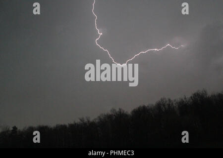 lightning bolt in sky above mountain - Stock Photo