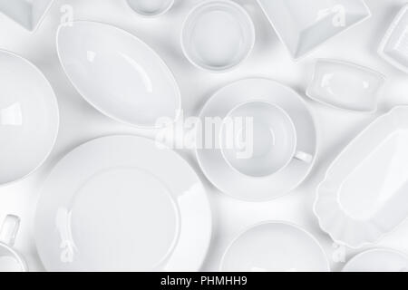 Empty, clean white assorted dishware with plates, cups and bowls white background - Stock Photo