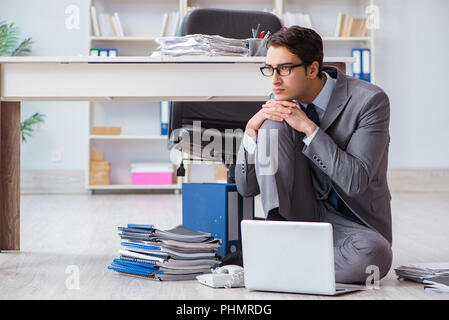 Businessman working and sitting on floor in office - Stock Photo