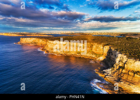 Steep sandstone cliffs of North Head plateau at the entrance to Sydney Harbour from open Pacific ocean - elevated aerial view towards distant city CBD