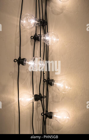 Vintage style light bulbs hanging from the wall - Stock Photo