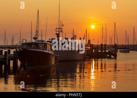 The sun rises over fishing boats and pleasure craft in Vineyard Haven Harbor in Tisbury, Massachusetts on Martha's Vineyard. - Stock Photo
