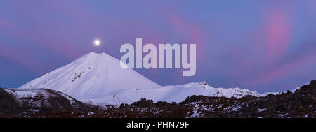 panorama of full moon over the Mount Ngauruhoe during sunrise in winter with pink cloud - Stock Photo