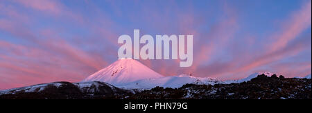 Panorama of an amazing sunrise and full moon over snow covered Mount Ngauruhoe Tongariro, National Park, New Zealand - Stock Photo