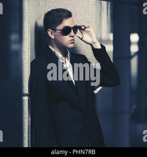 Young handsome man in sunglasses standing at the wall - Stock Photo