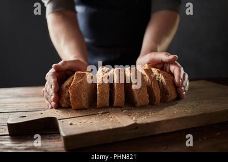 Fresh slice home bread in male's hands on wooden table - Stock Photo