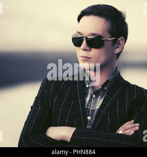 Young handsome fashion man in sunglasses at sunset - Stock Photo