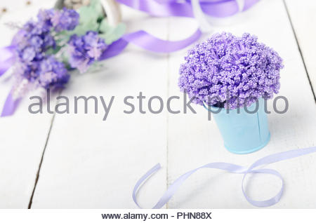 Violet flowers in blue metal bucket on white wooden table - Stock Photo