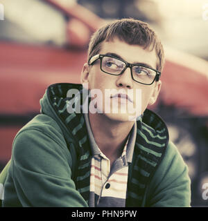 Sad young man wearing hoodie in city street - Stock Photo
