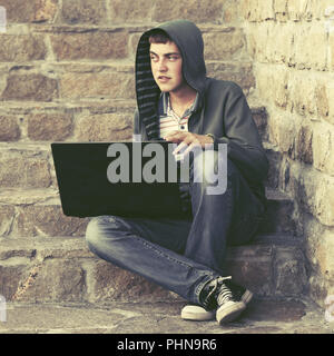 Young man in green hoodie using laptop on the steps - Stock Photo