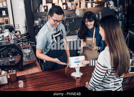customer self service order drink menu with tablet screen and pay bill online at cafe counter bar,seller coffee shop accept payment by mobile.digital  - Stock Photo