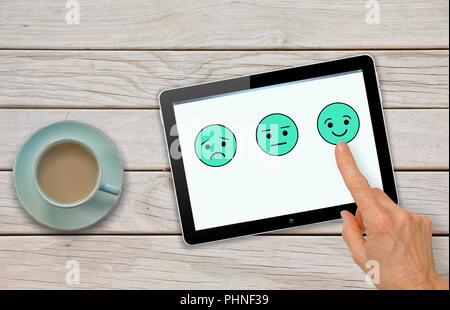 Customer satisfaction feedback survey questionnaire with hand choosing smiley - Stock Photo