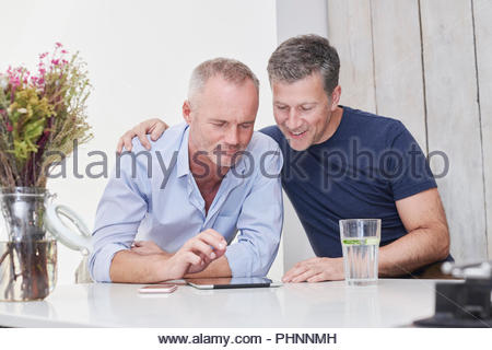 Gay couple using digital tablet in kitchen - Stock Photo