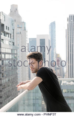 Young man leaning on balcony in New York City - Stock Photo