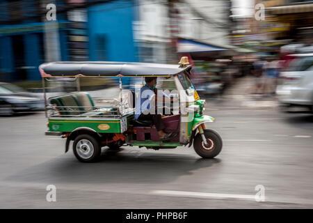 A tuk tuk moving on the streets of Bangkok - Stock Photo