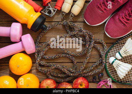 Fitness and healthy active lifestyle dieting background concept. Dumbbell, jump ropes, apples, badminton, oranges on wood background. Top view with co - Stock Photo