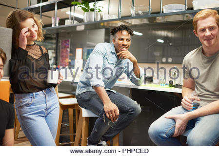 Colleagues talking in office kitchen - Stock Photo