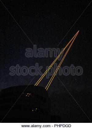 Lasers from a telescope during night at Paranal Observatory in Chile - Stock Photo