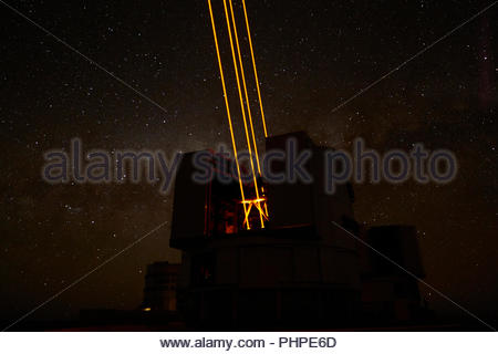 Lasers from a telescope at Paranal Observatory in Chile - Stock Photo