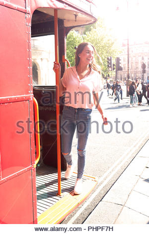 Young woman standing on bus - Stock Photo