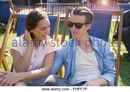 Couple sitting on deck chairs - Stock Photo