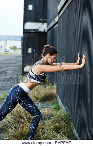 Woman stretching against wall - Stock Photo