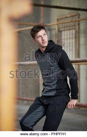Man wearing hoodie leaning on railing - Stock Photo