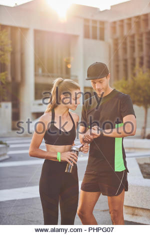 Couple wearing sportswear checking time - Stock Photo