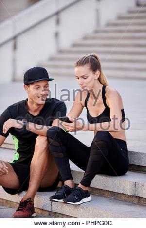 Couple wearing sportswear using smart phone - Stock Photo
