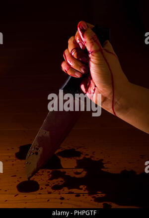 Hand of a murderer or killer soaked in blood and holding a knife ready to kill. Blood dripping on the floor. - Stock Photo