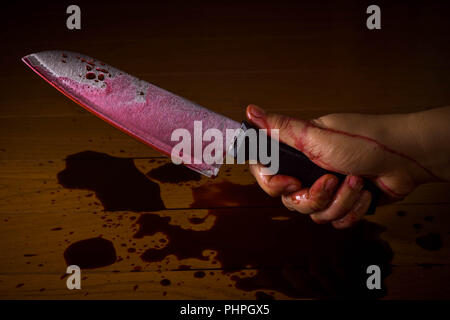 Hand of a murderer or killer soaked in blood and holding a knife ready to kill. - Stock Photo