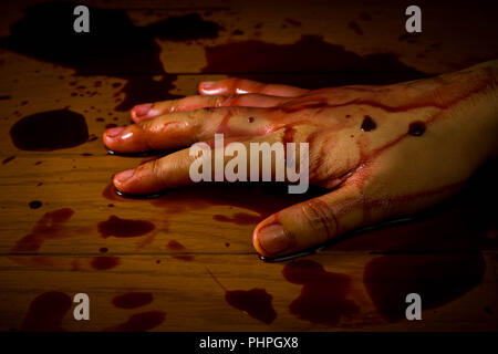 Murder, suicide or crime scene. Hand of a dead person soaked in blood on the floor. - Stock Photo
