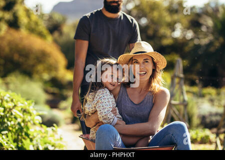 Man pushing woman and little girl in wheelbarrow. Mother and daughter ride in wheelbarrow pushed by father in farm. - Stock Photo