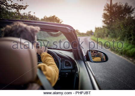 Man driving car on country road - Stock Photo