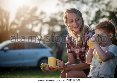 Mother and daughter holding mugs - Stock Photo