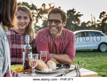 People smiling at picnic table - Stock Photo