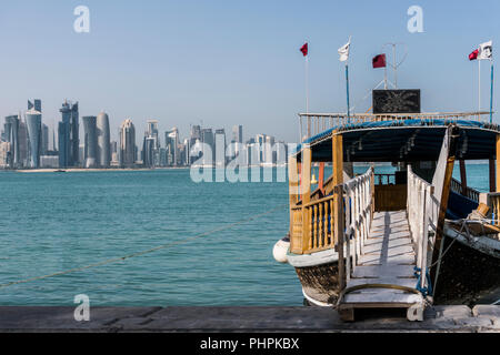 DOHA, QATAR - Feb 2018: Ladder from Corniche Broadway on Traditional Wooden Boat invite to Gulf City tourist Tour. Beautiful Doha Skyline View with with Floating Qatar Flags. Qatar, Middle East - Stock Photo