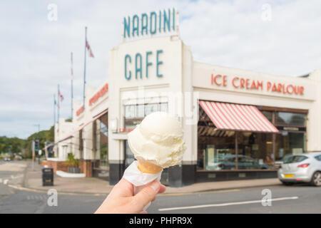 hand holding Nardinis ice cream cone outside Nardini Cafe and ice cream parlour, Largs, Scotland, UK - Stock Photo