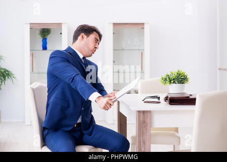 Bankrupt businessman angry and upset at home - Stock Photo